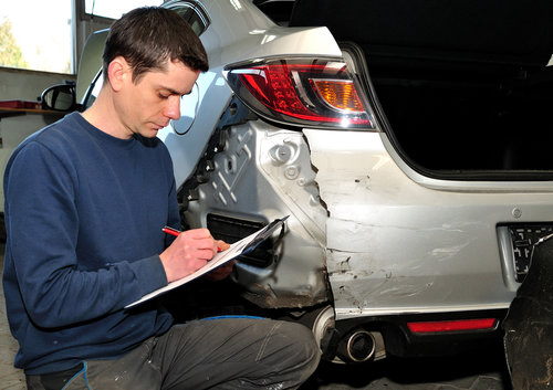 Insurance expert inspecting car damage.