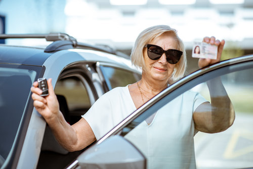Portrait of a happy senior woman showing driver's license and keys, standing near the car outdoors. Concept of an active people during retirement age
