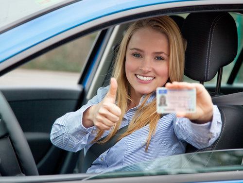 Attractive woman in car showing her european drivers license. Details on drivers license have been changed and blurred out.