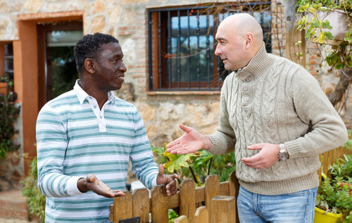 Neighbor conversation. Two smiling men breezily chatting near wooden wicket of rural house