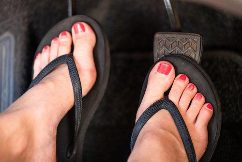 A girl is driving her car wearing flip flops.