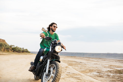 Handsome young man wearing casual outfit riding a motocycle at the beach