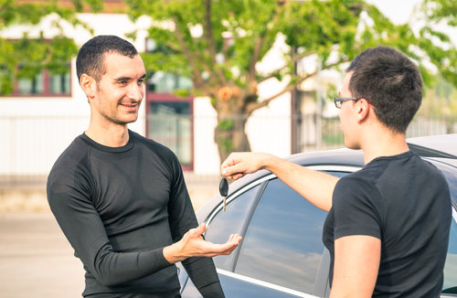 Happy satisfied young man receiving car keys after second hand sale - Concept business transport trade of modern luxury vehicles - Car rental assistance and insurance customer care