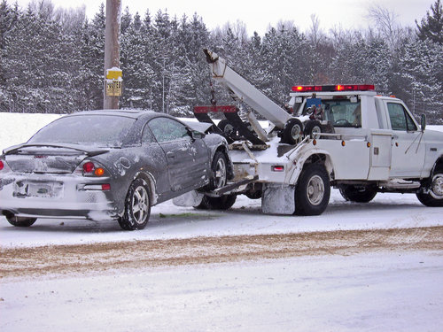 Tow truck hauling a wrecked car away in winter.